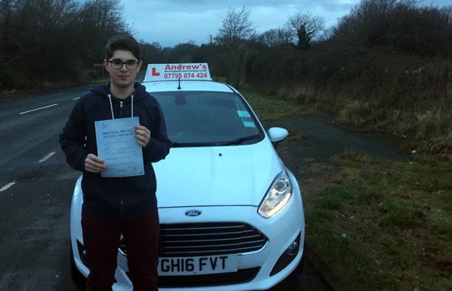 Lewis from Llandudno Junction standing by the car which he passed his driving test in.