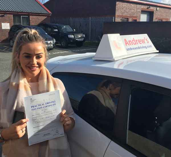 Anna in the Rhyl Driving Test Centre with a driving test pass certificate.